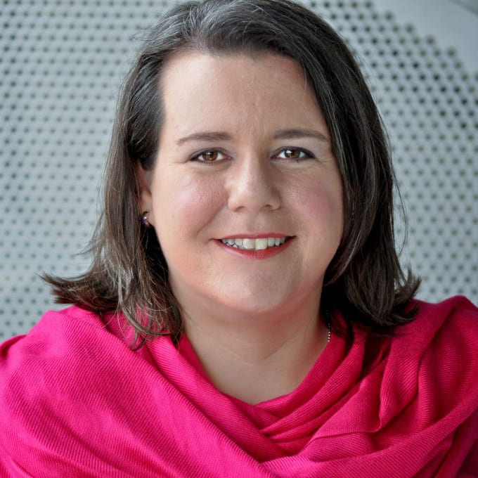 Photo of Antoinette Verdone wearing a pink scarf, gray grate in the background