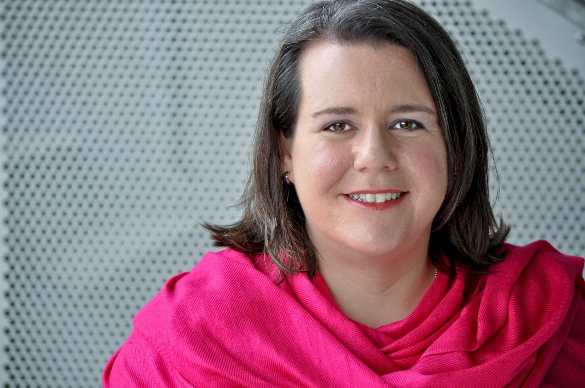 Picture of Antoinette Verdone wearing a pink scarf with a gray grate in the background